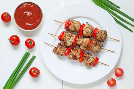 grilled meat: Traditional roasted turkey kebab skewer barbecue meat with vegetables and sauce on white dish. Served on kitchen table background. Rustic style, natural light. Stock Photo