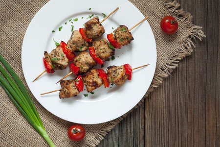 natureal: Traditional delicious turkey kebab skewer barbecue meat with tomatoes and green onion on white dish. Wooden vintage background. Rustic style, natureal light. Stock Photo