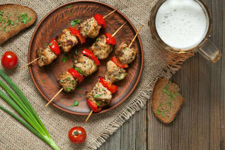 shashlik: Delicious roasted turkey or chicken kebab skewers meat barbecue on clay dish with tomatoes, green onion, wholegrain bread and beer. Vintage textile and wooden background. Rustic style and natural light. Stock Photo