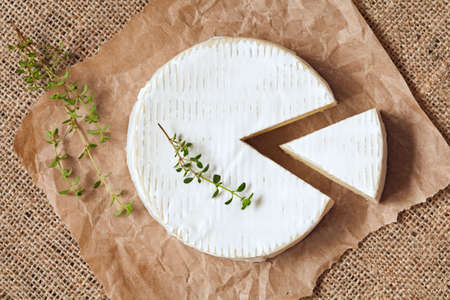 Sliced round camembert cheese traditional milk creamy dairy product with thyme on vintage parchment. Rustic style and natural light. Top view. Rustic sacking textile background.