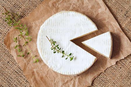 parchemin: Produit tranch� tour du camembert traditionnel de lait cr�meux laiti�re au thym sur parchemin vintage. Style rustique et la lumi�re naturelle. Vue d'en haut. Rustique fond limogeage de textile.