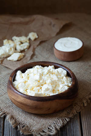 rustic food: Traditional homemade cottage cheese with sour cream in rustic wooden dish on vintage kitchen table background. Dark food photo, rustic style, natural light