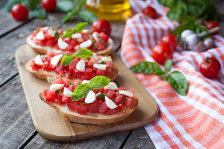 homemade style: Homemade traditional italian bruschetta antipasti with roasted baguette, tomatoes, basil and mozzarella on vintage wooden background. Rustic style and natural light.