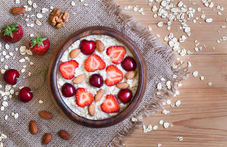 breakfast bowl: Delicious natural breakfast oatmeal porridge with strawberry, nuts and cherry in wooden bowl on vintage table background. Rustic style and natural light