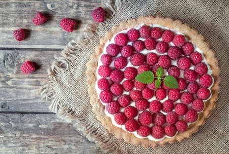빈티지 나무 테이블 배경에 크림과 민트와 직접 만든 전통적인 달콤한 나무 딸기 신랄한 파이. 소박한 스타일과 자연 채광.