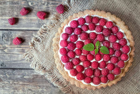 Homemade traditional sweet raspberry tart pie with cream and mint on vintage wooden table background. Rustic style and natural light. Archivio Fotografico