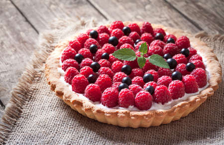 Delicious traditional homemade sweet raspberry tart cake dessert. Creamy pie with raspberries, whipped cream and mint on vintage rustic background. Rustic style and natural light.