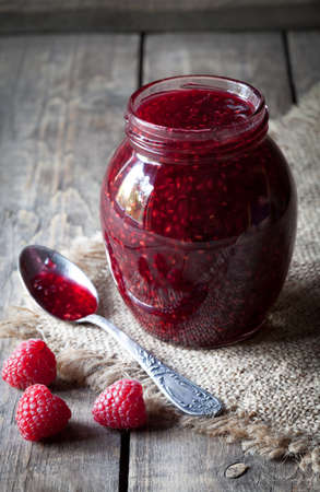 preserve: Raspberry jam sweet jelly preserve in mason jar. Delicious homemade organic marmelade with rustic spoon. Vintage wooden table background. Rustic style and natural light. Dark food photo.