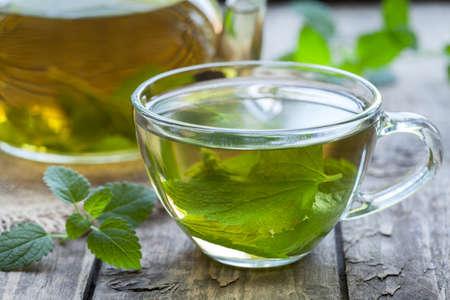 menta: T� natural fresca melissa verde de hierbas en la taza de cristal. Aromaterapia org�nica relajaci�n bebida m�dica saludable. R�stico fondo de la tabla de madera. Estilo r�stico luz natural.