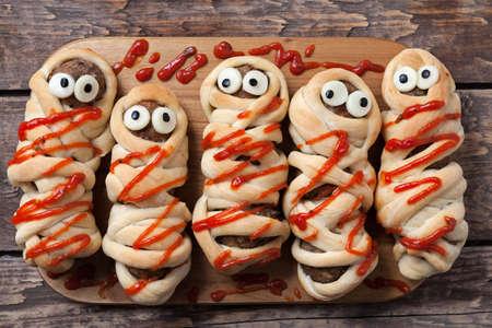 할로윈 집에서 만든 음식 소시지 미트볼 미라, 반죽에 싸서 구운 및 빈티지 나무 배경에 휴가 축하 파티를위한 가짜 혈액 소스 장식으로 덮여있다. 소 스톡 콘텐츠