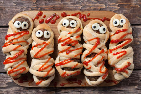 Halloween homemade food sausage meatball mummies wrapped in dough, baked and covered with fake blood sauce decoration for holiday celebration party on vintage wooden background. Rustic style and natural light.
