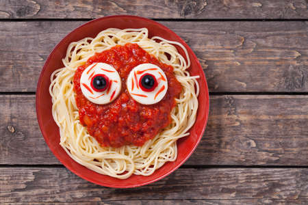 Scary halloween food pasta with big red eyes. Monster face for celebration party. Vintage wooden background.