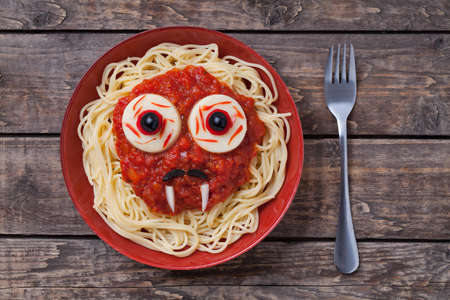 Halloween scary pasta food vampire face with big eyes and moustaches in red dish for celebration party decoration on vintage wooden table background