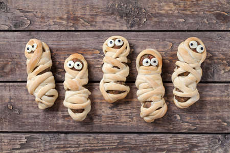 Homemade sausage meatball mummies wrapped in dough and baked for halloween celebration party. Vintage wooden background. Rustic style and natural light.