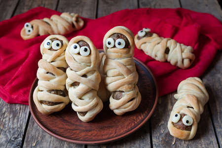 Scary halloween food meatball sausage mummies wrapped in dough with eyes  on vintage wooden background.  Halloween party decoration. Rustic style and natural light