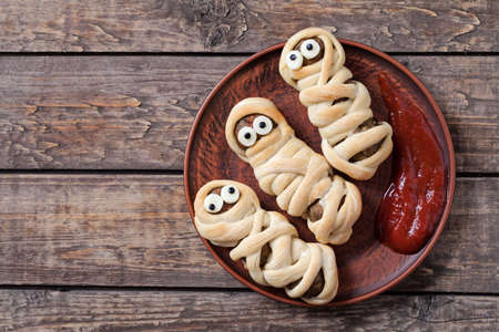 Mummy sausages scary halloween party food decoration wrapped in dough with blood sauce on clay dish. Vintage wooden background