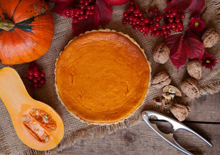 dessert table: Tasty traditional homemade pumpkin tart halloween celebration party sweet dessert treat with nuts and autumn composition on vintage wooden background. Rustic style and natural light