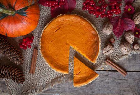 pumpkin: Rebanadas de pastel de tarta de calabaza dulce postre con canela, nueces y composici�n de oto�o sobre fondo de la tabla de la vendimia. Estilo r�stico y luz natural