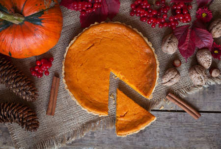 Sliced pumpkin tart cake sweet dessert with cinnamon, nuts and autumn composition on vintage table background. Rustic style and natural light