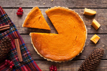 Homemade sliced pumpkin tart pie recipe with cinnamon and nuts on vintage wooden table background. Halloween party traditional dessert. Rustic style Reklamní fotografie