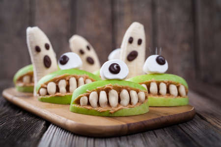 halloween: Scary edible halloween treat apple cyclop mouth with peanut butter teeth and banana ghosts chocolate face. Healthy natural vegetarian dessert recipe. Homemade party decoration sweets