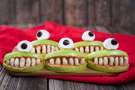 edible: Cute scary halloween apple cyclop monsters food healthy vegetarian celebration party snack dessert recipe with red fabric on vintage wooden background. Edible funny decoration