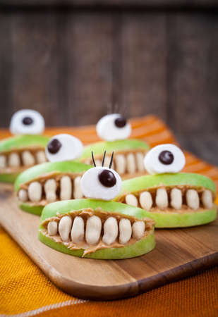 cyclops: Scary halloween food monsters healthy natural snack sweets for party decoration recipe. Homemade spooky apple cyclops mouth with teeth and peanut butter on vintage wooden table background.