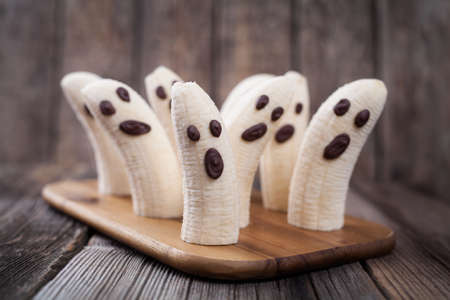 Homemade halloween scary banana ghosts monsters with chocolate faces. Healthy natural vegetarian snack recipe for party decoration on vintage wooden table background.