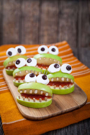 edible: Homemade scary halloween edible monsters for celebration eve party decoration. Natural healthy sweets food recipe. Cute apples mouth with eyes, sunflower seeds and jam on vintage wooden background. Stock Photo
