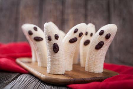 frutas divertidas: Homemade Halloween pl�tano miedo fantasmas monstruos con caras de chocolate. Merienda saludable vegetariana receta de postre divertido natural para la decoraci�n del partido en el fondo de la tabla de madera de �poca y tela roja. Foto de archivo