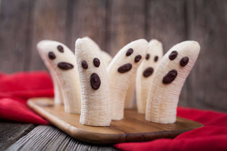 Homemade halloween scary banana ghosts monsters with chocolate faces. Healthy natural vegetarian snack funny dessert recipe for party decoration on vintage wooden table background and red fabric.