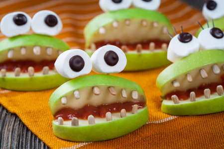 green eyes: Homemade halloween scary food monsters natural vegetarian snack. Celebration party decoration recipe. Cute apple mouth with eyes and sunflower seeds tooth on vintage wooden table background.
