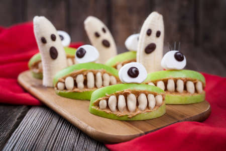 Funny halloween eadible monsters scary food healthy vegetarian snack dessert recipe for party decoration. Homemade spooky cyclop apples with teeth and banana ghosts on vintage wooden background. Natural treat Standard-Bild