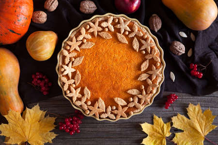 Homemade pumpkin tart pie organic sweet dessert food with various decoration on top. Traditional halloween or thanksgiving day healthy treat. Autumn composition on vintage wooden background. Rustic style.