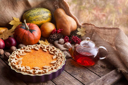 Traditional homemade pumpkin tart pie healthy natural sweet dessert recipe with tea. Halloween or thanksgiving holiday celebration meal. Autumn composition decoration and natural light. Vintage wooden background. Rustic style.