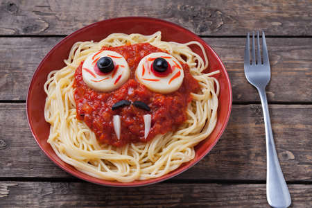 Halloween spaghetti face with big eyeballs fangs and moustaches in noodle dish with red tomato sauce, for halloween celebration party on vintage table background Archivio Fotografico
