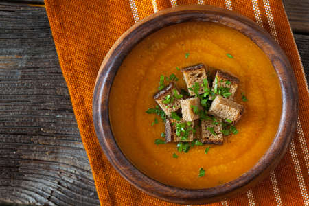 Natural vegetarian pumpkin cream soup with croutons delicious organic food recipe. Traditional halloween or thanksgiving day meal. Vintage wooden table background. Rustic style