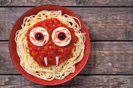spooky eyes: Scary halloween food pasta vampire monster face with big eyes and fangs for celebration party decoration. Vintage wooden background Rustic style Stock Photo