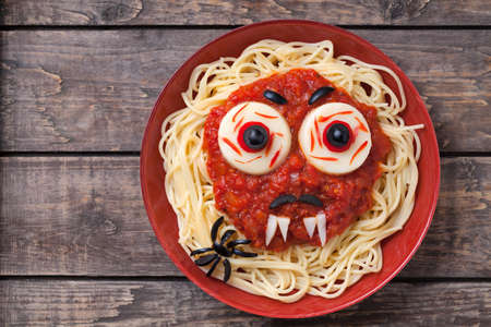 Halloween party creative decoration food. Spaghetti monster face with big eyeballs, fangs, spider and moustaches in red dish on vintage wooden table background. Archivio Fotografico