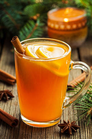 Traditional hot toddy winter drink with spices recipe. Healthy organic homemade holiday celebration beverage in glass. Vintage wooden background. Rustic style.