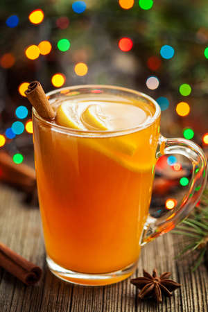 stick of cinnamon: Traditional hot apple cider alcohol drink winter season refreshment juice. Healthy organic christmas or thanksgiving beverage with spices. Hot steam and colorful boke. Vintage wooden background. Rustic style. Stock Photo