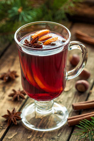 grog: Traditional grog hot alcohol spiced drink recipe. Homemade winter christmas or thanksgiving holiday aromatic refreshment beverage with orange, cinnamon, anise and other spices. Vintage wooden background. Rustic style.