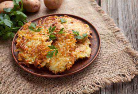 전통적인 감자 팬케이크 또는 latke 수 제 유대인 음식 하누카 축 하 요리법. 수 제 유기농 완전 채식 식사 빈티지 나무 배경에 클레이 접시에. 소박한 스 스톡 콘텐츠