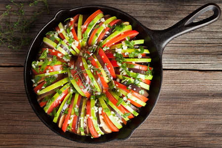 cast iron pan: Traditional raw vegetable ratatouille in cast iron pan preparation recipe homemade healthy vegetarian food on vintage wooden table background. Rustic style and natural light. Top view.