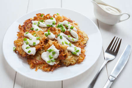 potato: White plate of potato pancakes or latke traditional homemade vegan food with greens and sour cream on white vintage wooden table background. Rustic style and natural light.