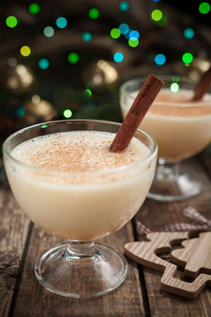 non alcoholic: Eggnog traditional christmas celebration homemade egg vanilla milk non alcoholic drink preparation recipe in two glass cups on vintage wooden background. Green and blue bokeh, shallow depth of field. Rustic style. Stock Photo