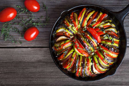 Vegetable ratatouille baked in cast iron frying pan homemade preparation recipe healthy diet french vegetarian food on vintage wooden table background. Top view. Rustic style.