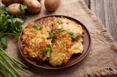 fritter: Potato pancakes or latke traditional homemade fried vegetable food recipe. Healthy organic vegan food. Rustic style Stock Photo