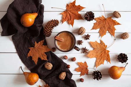 Composizione in autunno con la tazza calda di caffè con cannella, sciarpa, noci e foglie. Concetto di mattina accogliente, il comfort, il relax, la malinconia, cadere tempo, a casa. Vintage tavolo sfondo bianco. Stile rustico. Archivio Fotografico - 49229363