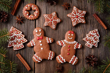 fur trees: Gingerbread man and woman couple, fur trees, star, christmas cookies composition with xmas tree decoration on vintage wooden table background. Homemade tradition dessert food recipe. Rustic style.